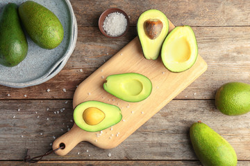 Flat lay composition with ripe avocados on wooden background