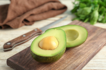 Wooden board with cut avocado on table