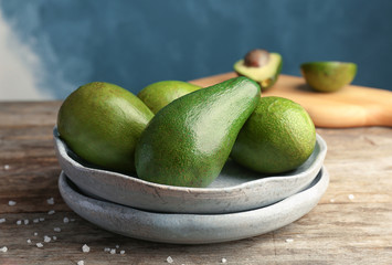 Plate with ripe avocados on wooden table