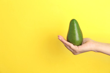 Woman holding ripe avocado on color background