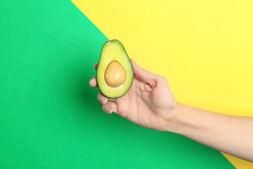 Woman holding ripe cut avocado on color background