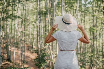 Blonde woman with hat in the forest
