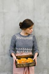 Woman at wall with corn