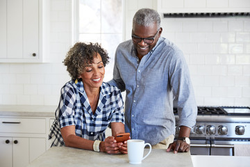 African American Senior Couple looking at cell phone in the kitchen together