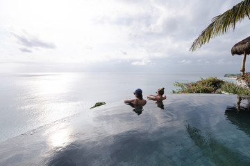 Two young attractive women relaxing in an infinity pool