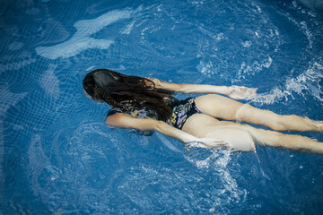 Beautiful young woman in the pool