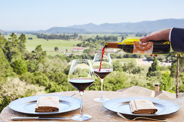 Sommelier pouring red wine into glasses overlooking view of Napa Valley, California