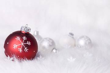 Christmas red snowflake themed baubles and snowflake decorations on a soft wintery fur white background