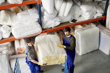 Workers Carrying Mattress Package In Warehouse At Sofa Workshop