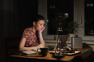 Thoughtful woman at laptop in evening