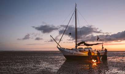 Two friends stay warm during there adventure  after they got stuck with their sailboat on a sandbank when being surprised by low tide