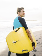 Man with board on tropical beach