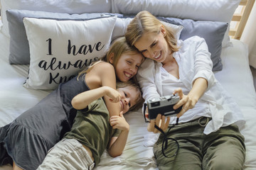 Family taking selfie with film camera at bed