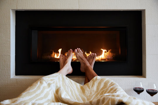 Couple relaxing in front of fireplace with wine