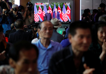 People watch a TV broadcasting a news report on summit between the U.S. and North Korea, in Seoul