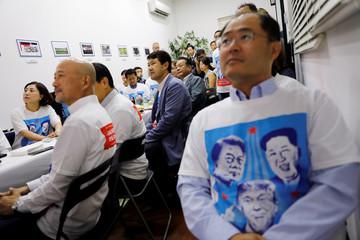 Koreans watch as U.S. President Donald Trump meets North Korean leader Kim Jong Un, on television at the Korean Association in Singapore