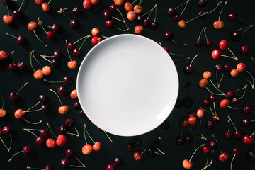 top view of empty round white plate and sweet ripe cherries on black background