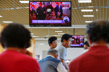 People watch from a shopping mall food court  in the Los Angeles neighborhood of Koreatown as Singapore hosts a summit between U.S. President Donald Trump and North Korean leader Kim Jong Un in Los Angeles
