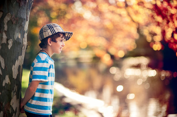 Boy smiling while standing under a tree in autumn
