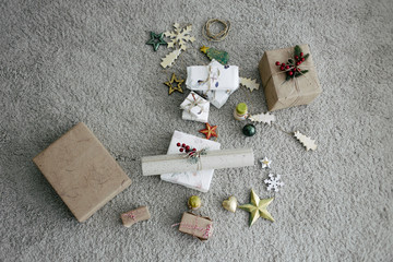 Christmas present wrapped in natural handmade gift paper and ornament on the grey carpet