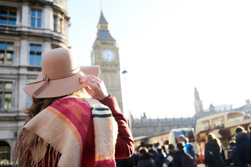Woman in hat and scarf over shoulder against Big Ben.