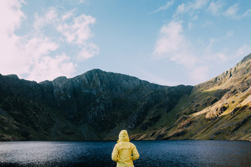 A person in a yellow jacket looking out towards a lake and mountain in Wales