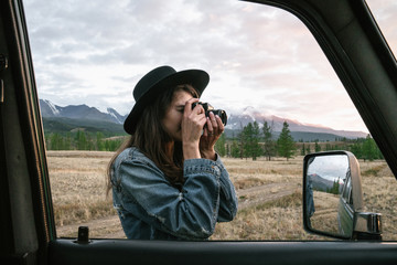 Anonymous young woman taking pictures near old green jeep in wild area