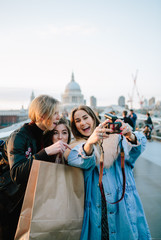 Cute twenties friends laughing and taking at photos  in front of St Pauls Cathedral, London