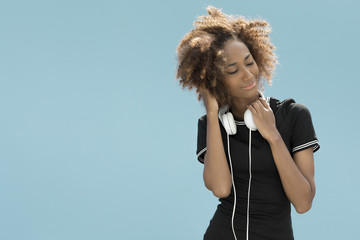 Young woman with headphones in front of a blue wall.