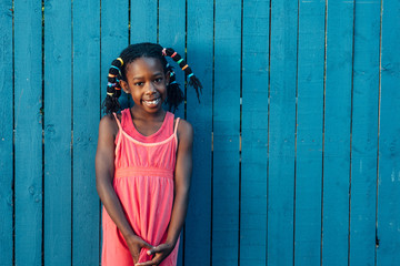 Black girl with fun hair next to a blue fence