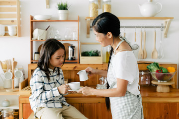 Asian mother and son drinking tea together at home