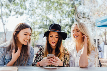 Three Friends Sit and Look at Cell Phone