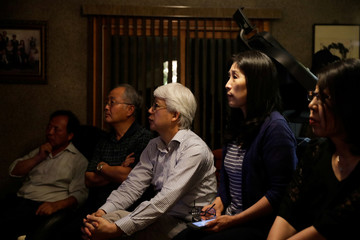 People watch a TV broadcasting a news report on the summit between the U.S. and North Korea, in Little Neck, New York
