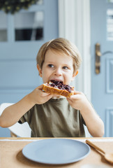 Young boy eating toast with jam for breakfast