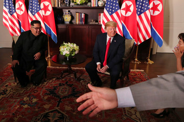 U.S. President Donald Trump and North Korea's leader Kim Jong Un smile before their meeting in Singapore