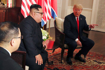 U.S. President Donald Trump gestures next to North Korea's leader Kim Jong Un before their meeting in Singapore