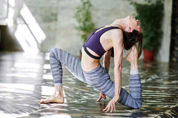 Woman having advanced yoga class