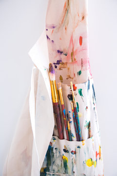 Close-up of a painters apron covered in paint hanging from a wall.