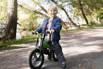 Excited toddler on his roller bike