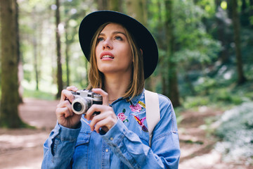 Young woman taking photos with vintage camera in the woods.