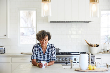 Senior African American woman in her kitchen drinking coffee
