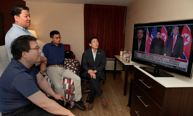 North Korean defectors Park Sang Hak and Justin Kim watch replays of President Donald Trump's summit meeting in Singapore with North Korea's Kim Jung Un on television, at a motel in Leesburg