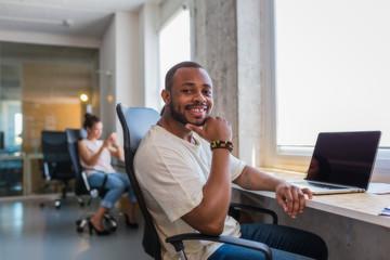 Black man at the office smiling at camera