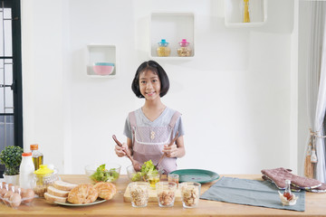 Little girl cooks in the kitchen at home