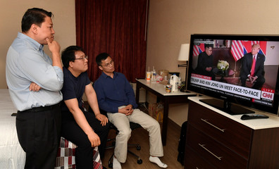 North Korean defector Justin Kim watches  replays of President Donald Trump's summit meeting in Singapore with North Korea's Kim Jung Un on television, at a motel in Leesburg