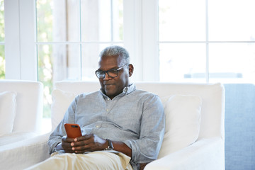 African American Senior man texting on a smart phone sitting on the couch at home