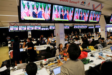 A TV screen shows news report about the meeting between U.S. President Donald Trump and North Korea's leader Kim Jong Un at a media center for the summit, in Singapore