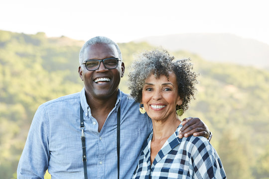 Portrait of senior African American senior couple in nature with camera
