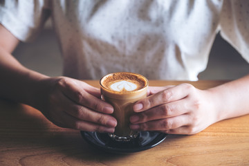 Closeup image of woman's hands holding a glass of hot coffee with heart latte art on wooden vintage table