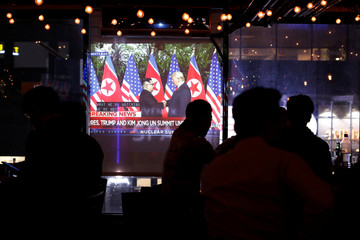 People gather in the WABar to watch a broadcast on television as U.S. President Donald Trump meets North Korean leader Kim Jong Un in the Korea Town section of Manhattan, New York